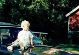 liten Johan Niklasson på motorhuv vid röd stuga